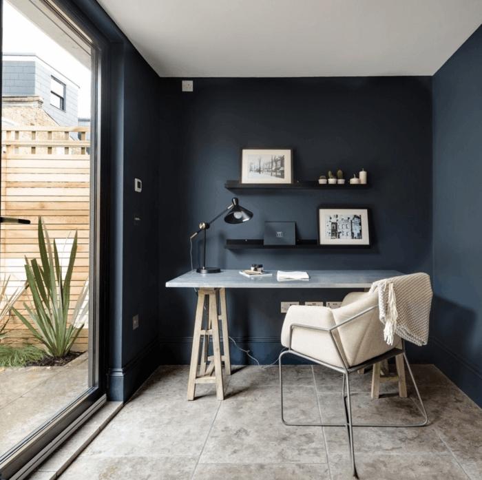 decoracion nordica salon, despacho pequeño con ventanal y terraza, paredes en azul oscuro, mesa con piernas de madera y encimera de plástico, silla tapizada con cuero, cuadros enmarcados