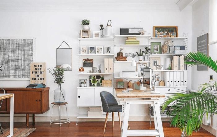 salon nordico, despacho vintage con estantería blanca, palmera decorativa, silla tapizada gris, suelo laminado, mueble auxiliar bajo retro, espejo en la pared