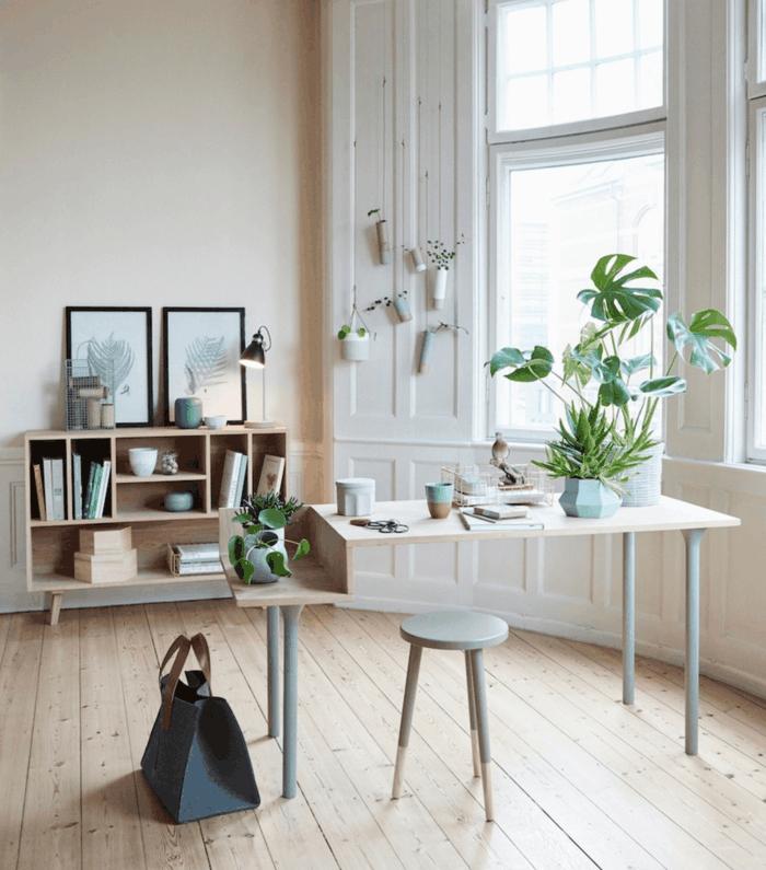 salon nordico, plantas verdes, escritotio con sillasin respaldo, estanterñia baja de madera clara, techos altos, ventanas grandes, tarima, cuadros