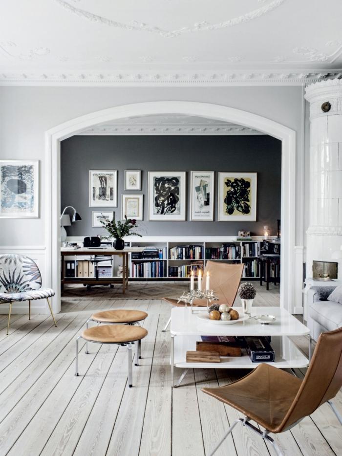 decoracion nórdica, espacio grande, sala de star con tarima, silla y taburetes de cuero marrón, pared de acento en gris, estanterñiaa baja de lbros, cuadros enmarcados, chimenea antigua