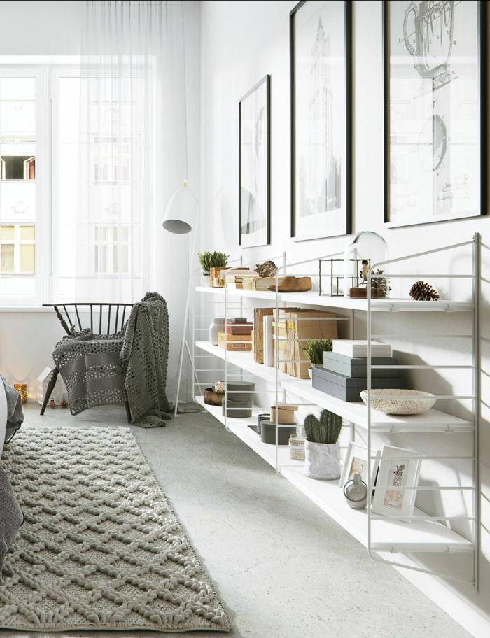 salon en blanco y gris, estilo nordico, alfombra de ganchillo, estantería de tres niveles blanca de metal y madera, silla con cubierta tejida, dibujos arquitectónicos en marcos negros