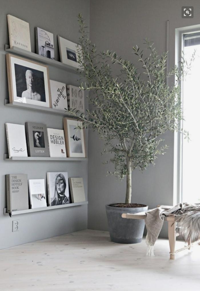 habitación gris, detalle de salón, pared gris, estantes de metal con libros de arte, arbol decorativo en maceta, suelo de mármol