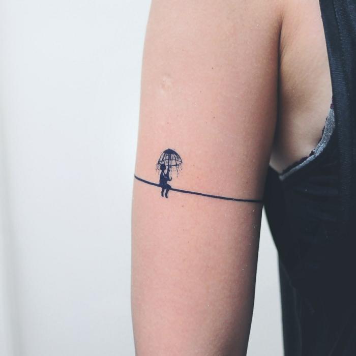 tatuajes pequeños, brazo mujer delgada, tatuaje tipo brazalete con niña bajo la lluvia con paraguas, color azul oscuro