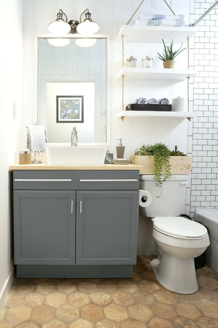 estilo moderno, mueble lavabo con puertas de madera gris, ducha con bañera, estantería de cuerda y madera con plantas verdes, espejo grande, cuartos de baño pequeños