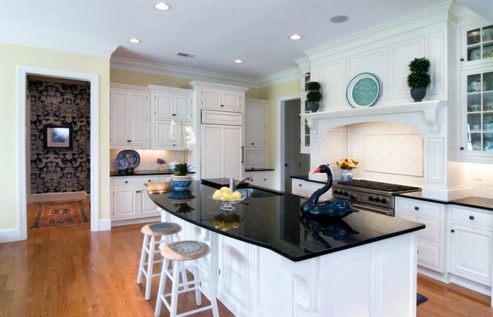 barra grande con encimera de marmol, dos sillas pequeñas, paredes en blanco con interesantes elementos arquitectónicos, cocina abierta moderna