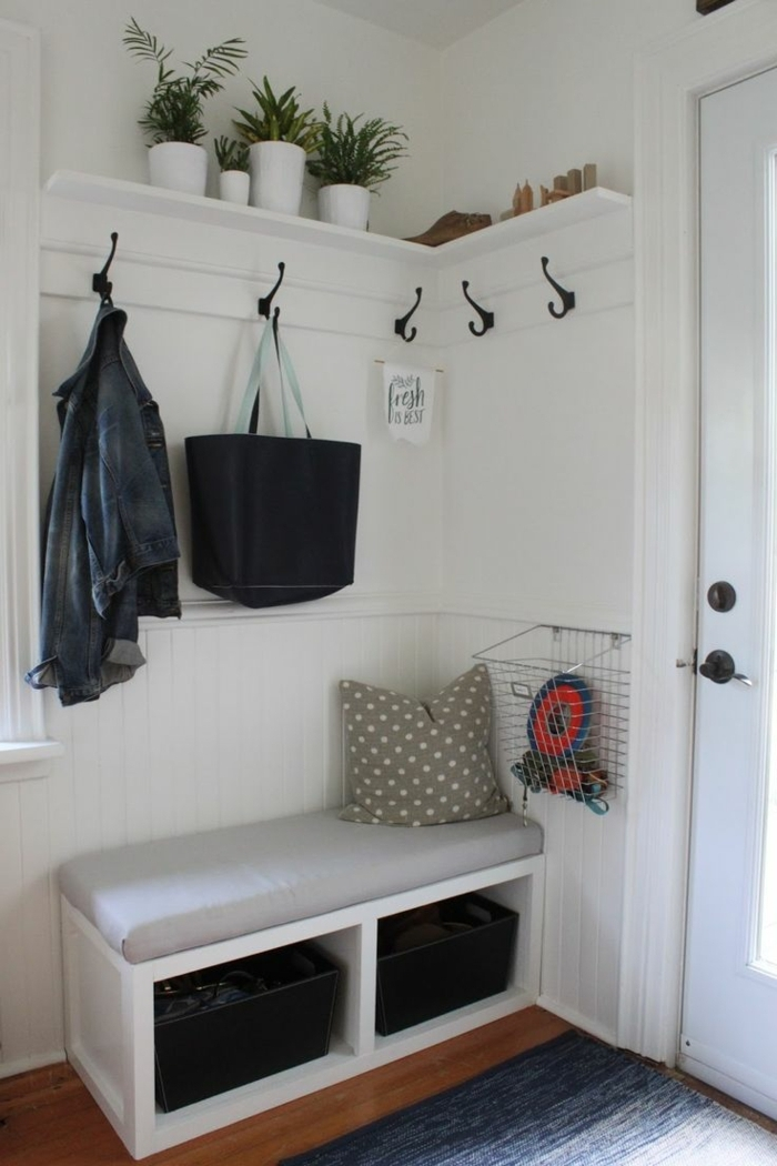 rincón acogedor decorado en blanco con banco multifuncional, muebles entrada de doble función, decoración de plantas verdes