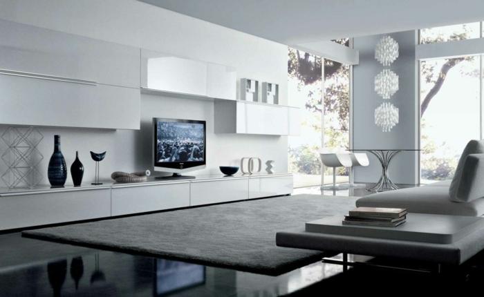 ambiente moderno decorado en blanco y gris, muebles de salon modernos de diseño, grandes ventanales y preciosos objetos decorativos