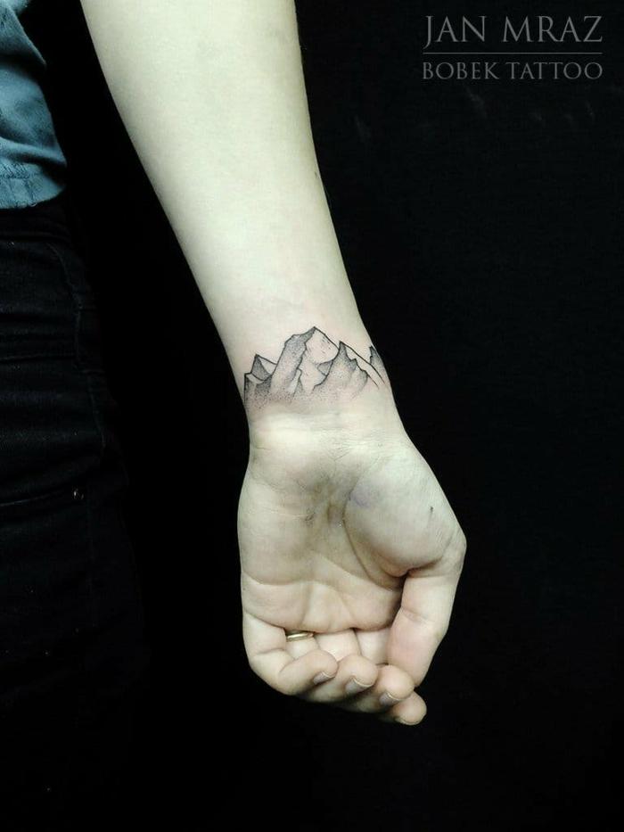 tatuaje moderno con efecto 3D, muñeca parte interior, cadena montañosa, mano mujer con anillo, tatuajes pequeños para mujeres originales