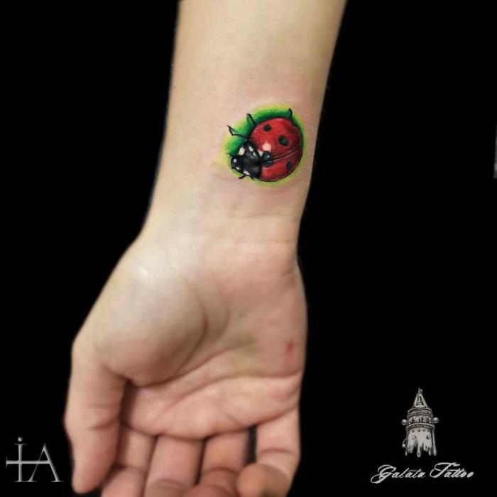 tatuajes en la muñeca, diseño de tattoo pequeño de color, mariquita en rojo y verde, parte interior de la muñeca