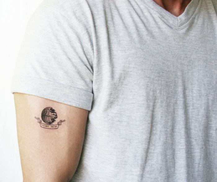 hombre con brazo musculoso, tatuaje pequeño de imagen y frase, camiseta gris, tatuajes simbolicos