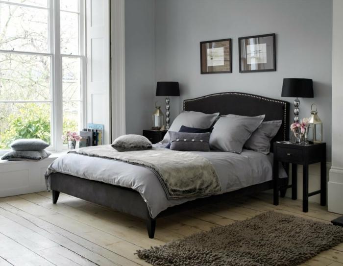 dormitorio con ventana grande, vista al jardin, suelo de tarima, paredes y ropa de cama grises, tapete marron peludo, habitación gris