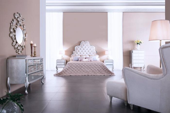 precioso dormitorio decorado en estilo vintage, paredes en color rosa y espejos decorativos ornamentados, cama con cabecero en capitoné