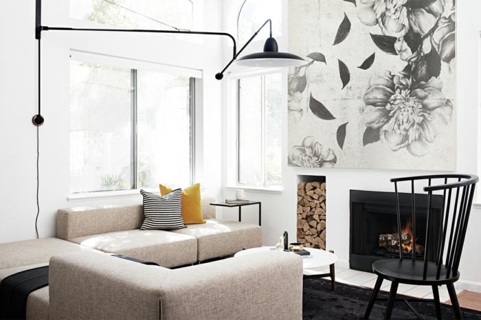 salon pequeño con chimenea, pared con nicho de almacenamiento de leña, sofá beige con cojines en amarillo y blanco y negro rayos, pintura grande, mesita baja redonda, ventanas sin cortinas, decoracion nordica