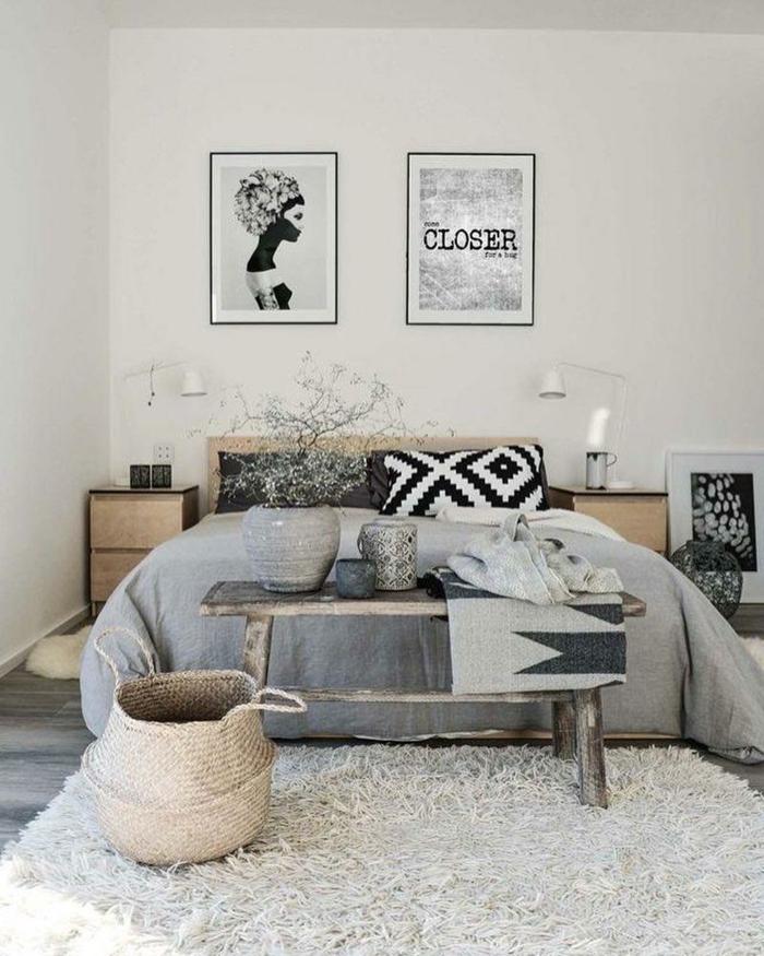 decoracion moderna estilo escandinavo, habitacion gris y blanca, cama matrimonio, posteres en blanco y negro, tapete peludo, banco de madera