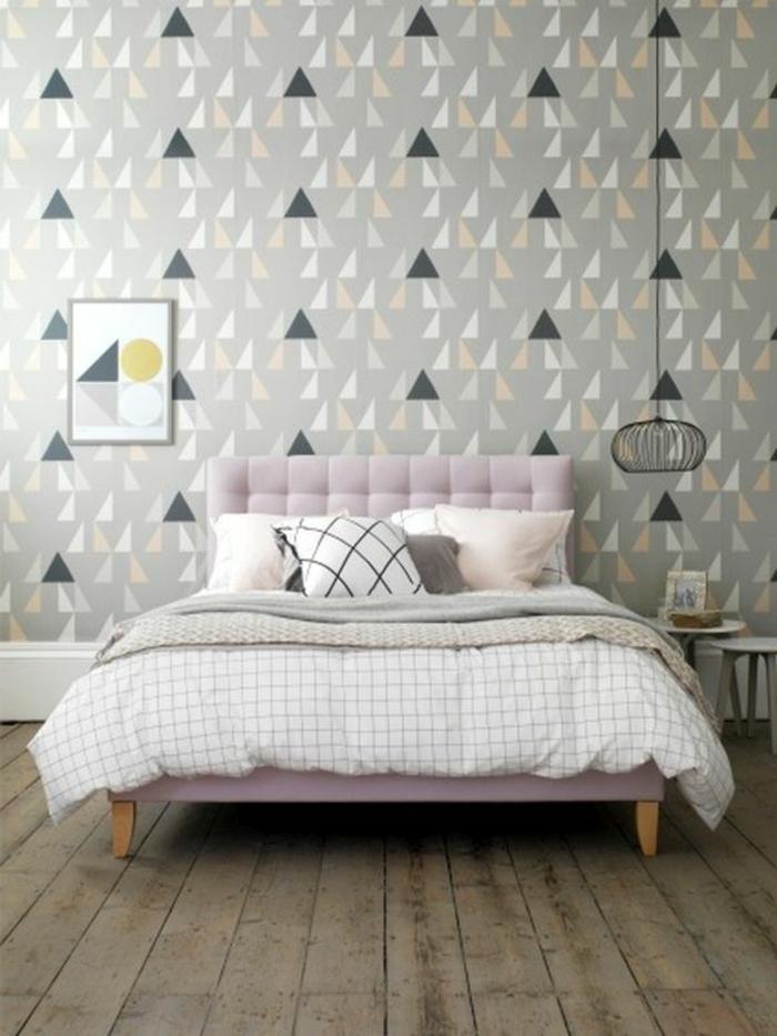 dormitorio moderno con papel pintado en triángulos, cama con cabecero en capitoné rosado, habitacion gris, suelo con tarima, lampara colgante