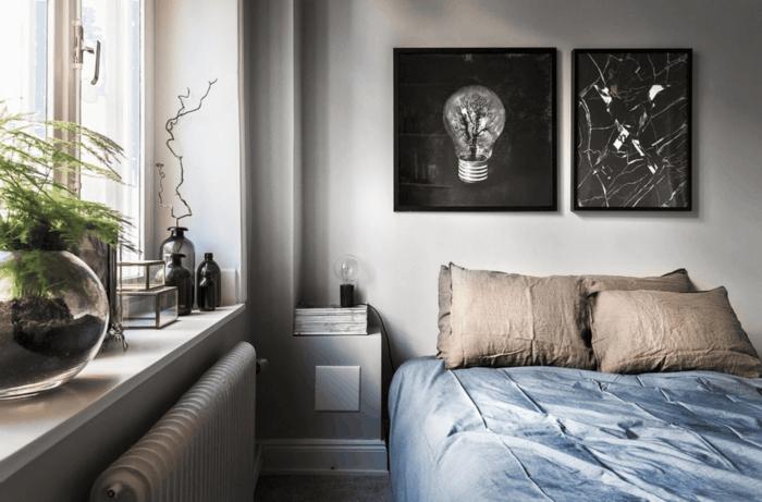 dormitorio nordico, espacio pequeño, ventana con plantas verdes, cuadros en blanco y negro, ropa cama en azul grisáceo y beige