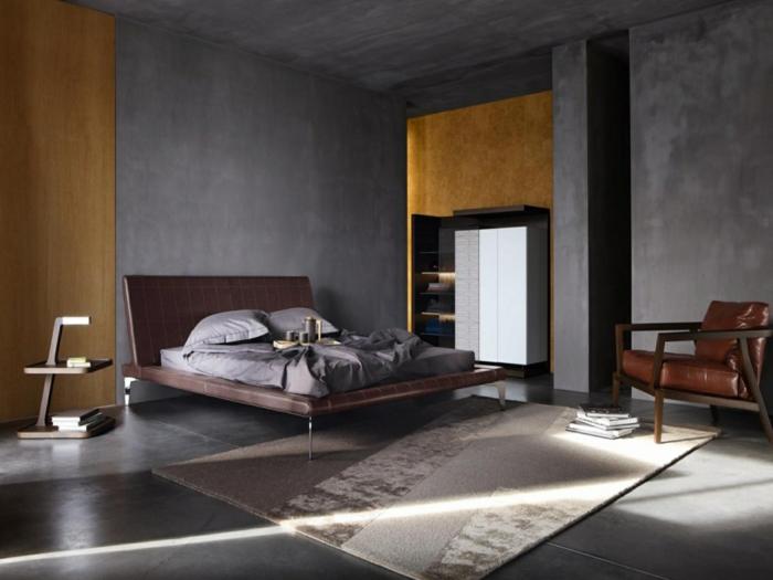 decoracion habitacion matrimonio, dormitorio moderno grande, techo alto, paredes en grris y amarillo, cama doble tapizada de cuero, suelo con baldosas y alfombra, sillon