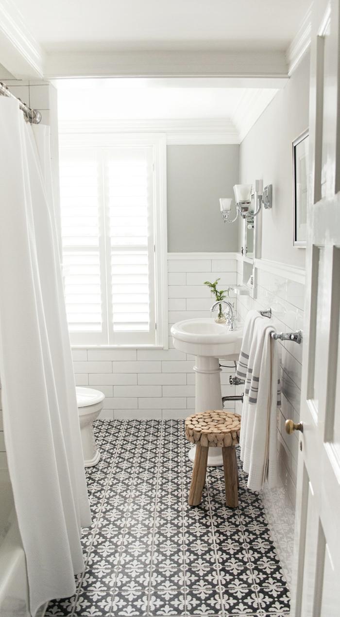 baño pequeño con mucha luz, decoracion en blanco y gris, duchas de obra, suelo con baldosas de patron floral, taburete de madera, ducha con cortina