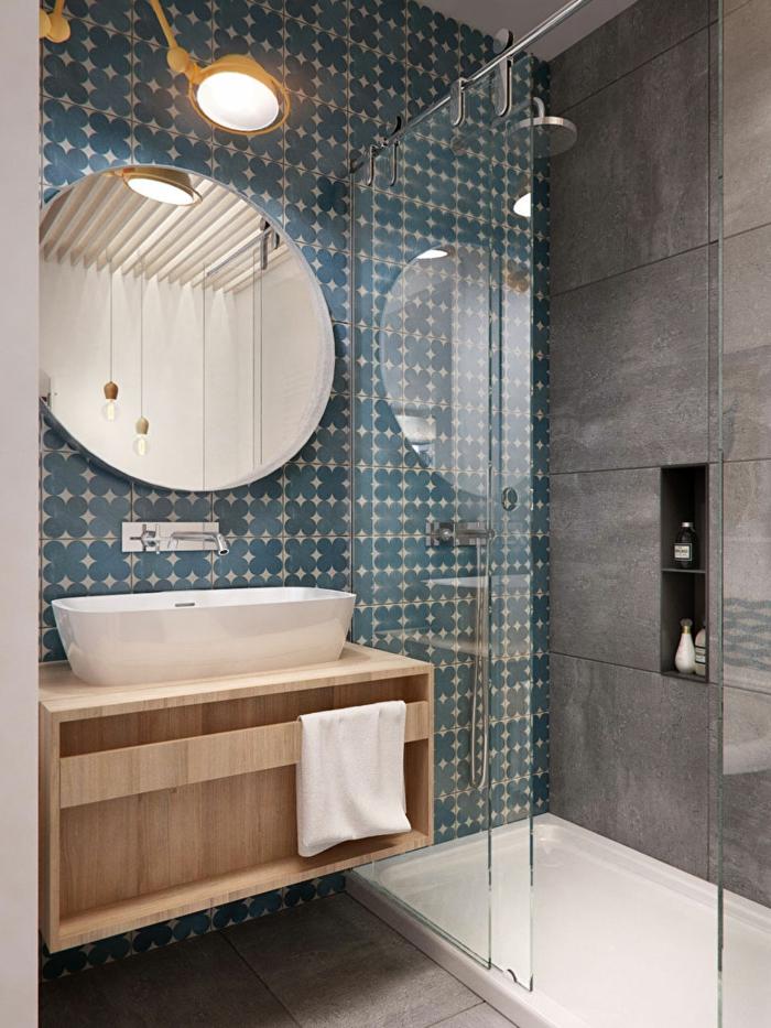 ideas baños pequeños, ducha con plato, espejo grande redondo, pared con papel pintado en treboles en azul grisaceo, mueble lavabo de madera, lampara con brazo