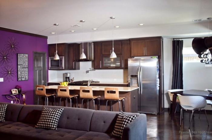 sala de estar moderna con cocina abierta, pared en color lila con decoracion como punto focal, pequeño comedor
