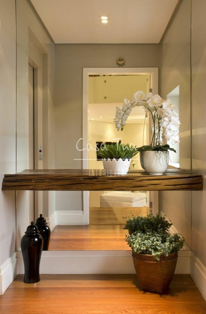 ejemplos de recibidores originales, decoración con plantas verdes y orquídeas, luces empotradas en el techo y paredes en color ocre