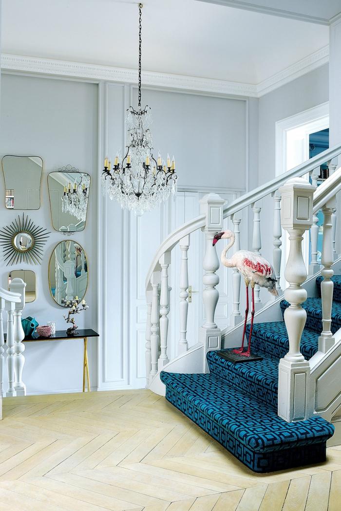 recibidor de encanto con decoración en estilo vintage, espejos vintage y candelabro bonito, escaleras tapizadas en azul y negro