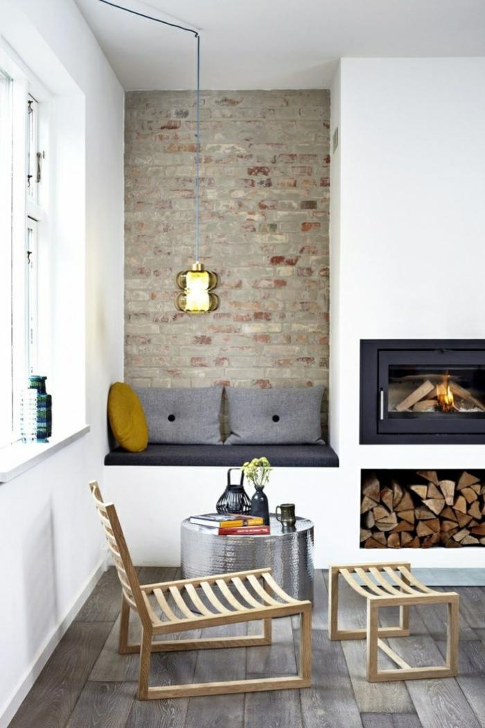 habitación pequeña, chimenea encendida, muebles estilo nordico, nicho almacenamiento de leña, pared de ladrillo visto, rincón de lectura, sillón con taburete de madera, mesa redonda baja