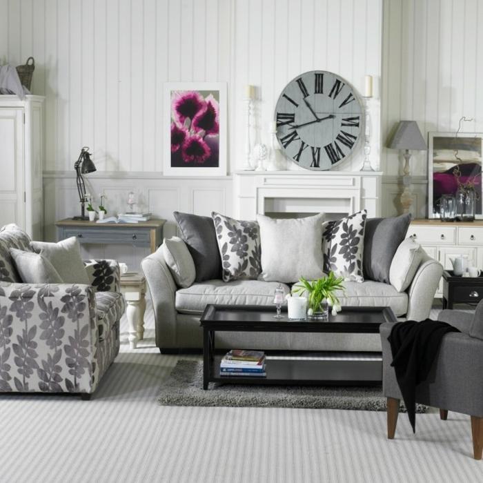salones con encanto, colores para habitaciones, salon epqueño, paredes con listones blancos, sofá gris con cojines de motivos florales, reloj de pard redondo, cuadro con flores ciclamen