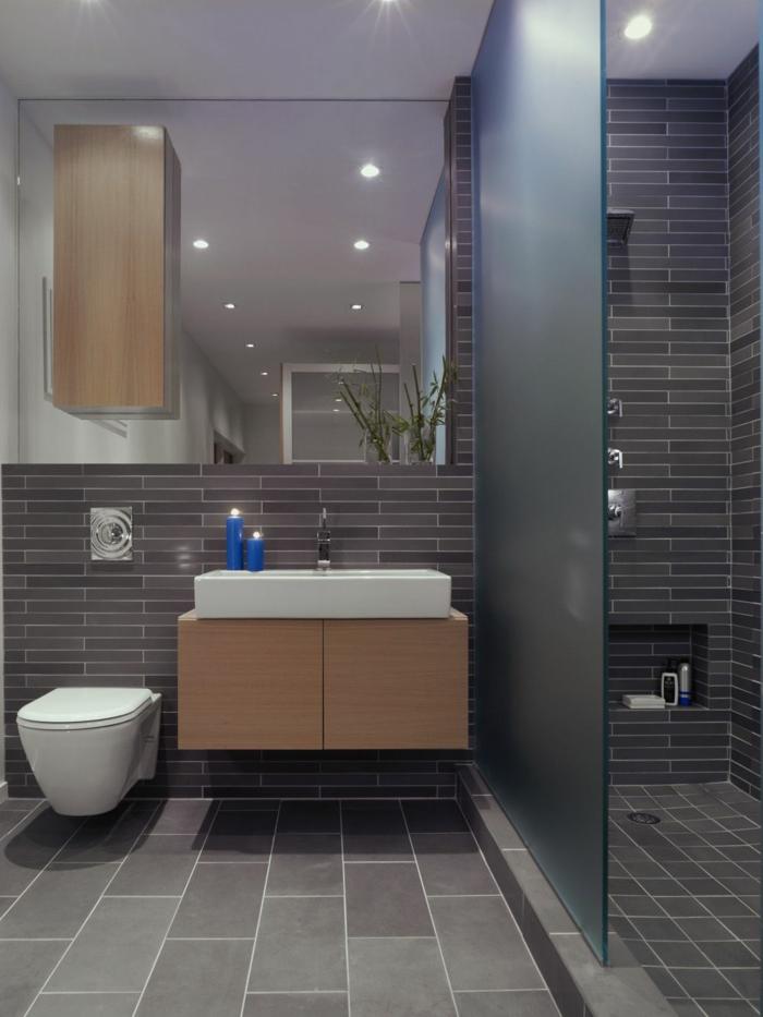 baño en estilo contemporaneo, colores oscuros, ducha de obra, mampara de vidrio mate, espejo grande, luces empotradas en el techo, lavabo rectangular con candelas azules