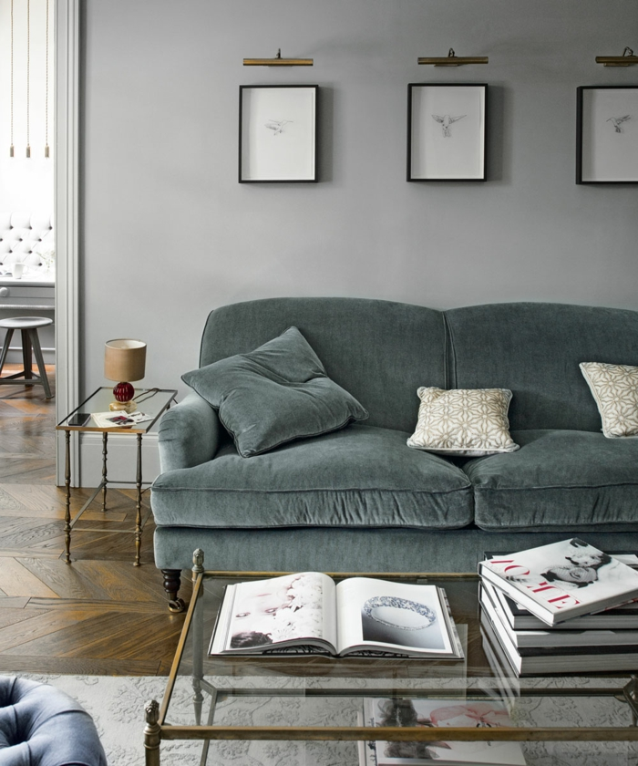 salon pequeño, sofá tapizado en terciopelo, mesa de vidrio, bocetos enmarcados, suelo con parquet y alfombra, habitación gris