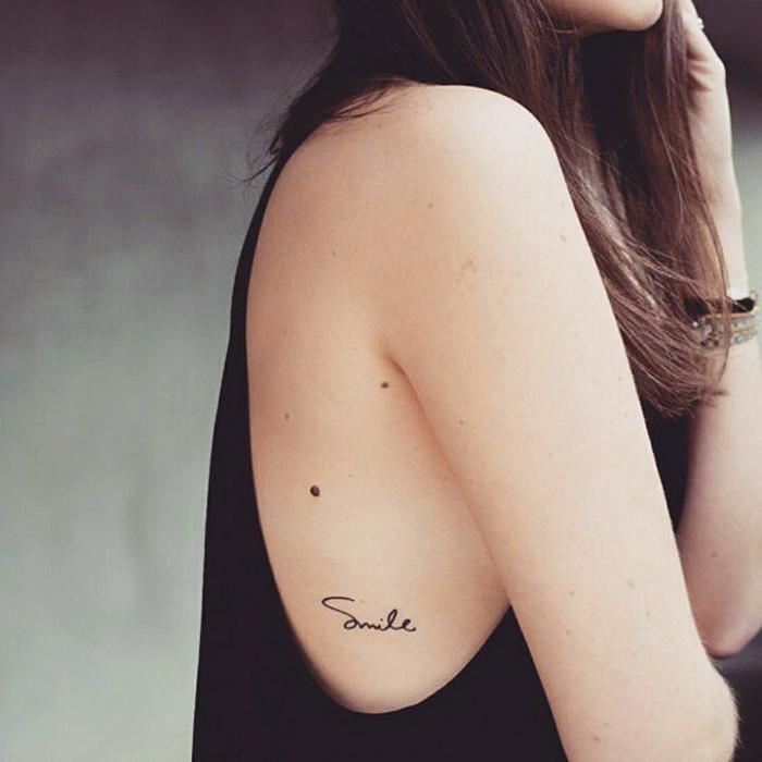 tatuajes originales, mujer con pelo largo, tatuaje frase en el torso, fondo en cursiva, color negro, smile