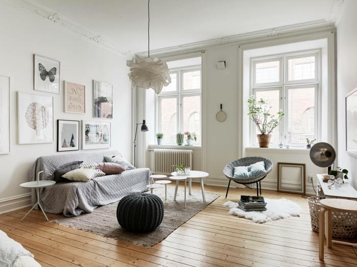 dormitorio nordico, sala con mucha luz natural, sofá gris con cojines, tapete. puf negro de ganchillo, silla acapulco, mesitas redondas blancas, decoración con cuadros, plantas