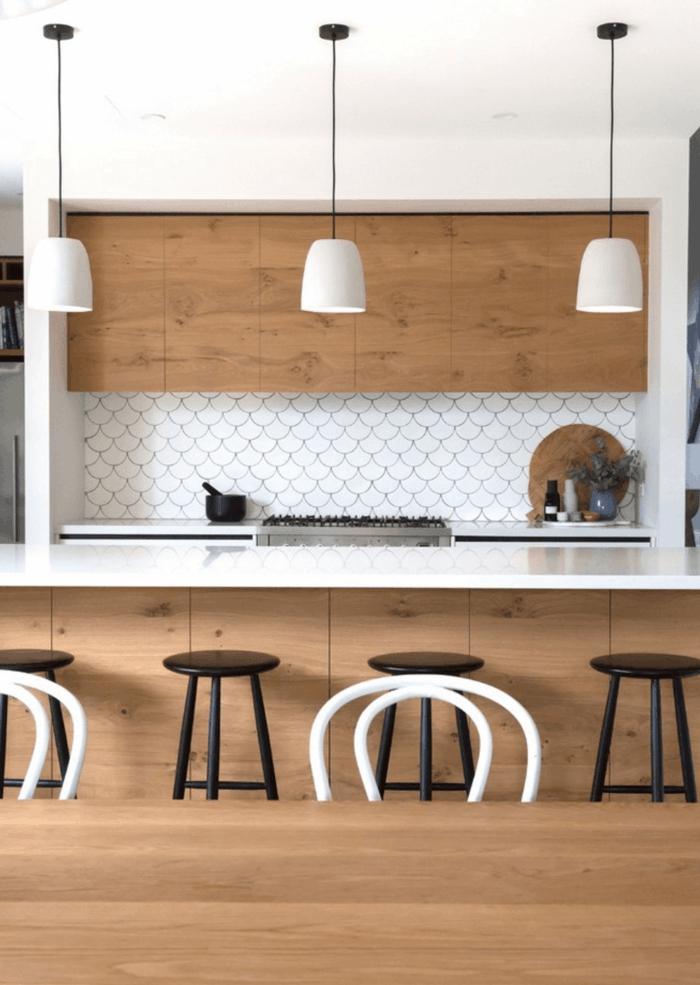 cocina comedor, decoracion nordica, cocina con isla y encimera de p'lástico, sillas negras de barra, madera clara, lámparas colgantes