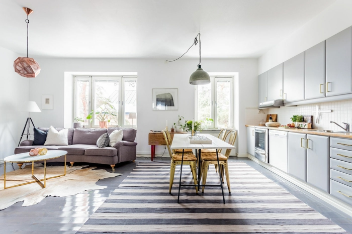 salon comedor, decoracion nordica, colores para habitaciones, tapete piel de vaca, tapete rayado, suelo laminado, sofá lilá con cojines, lámparas colgantes, ventanas grandes