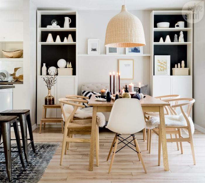 muebles estilo nordico, salon comedor pequeño, sofá beige en capitoné, estanterías paralelas, mesa con velas, sillas de madera, suelo laminado, lámpara colgante grande
