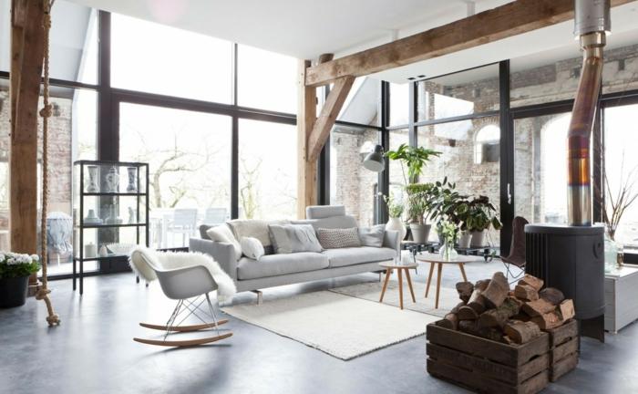 slon grande, decoracion nordica, chimenea de metal, vigas de madera, sofá gris, tapete beige, paredes de vidrio, rincón con plantas verdes