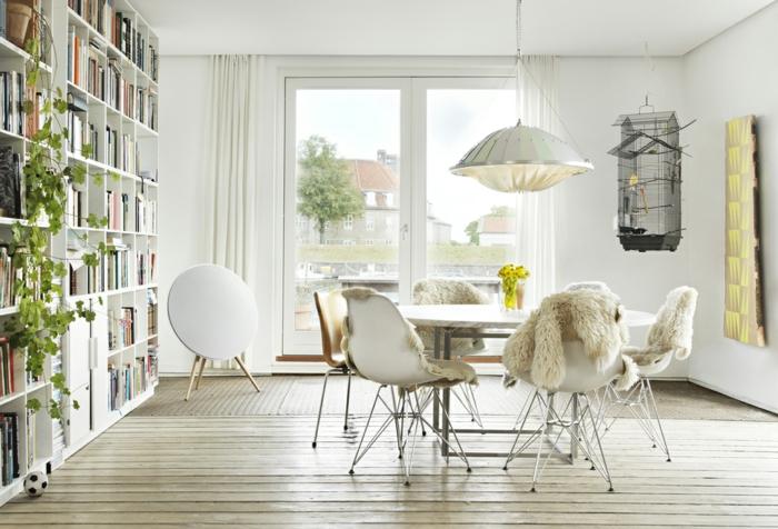 comedor con paredes y muebles blancos, jaula para pájaros, mesa redonda, decoracion nordica, sillas con cubiertas de lana, librería alta con planta verde trepadora