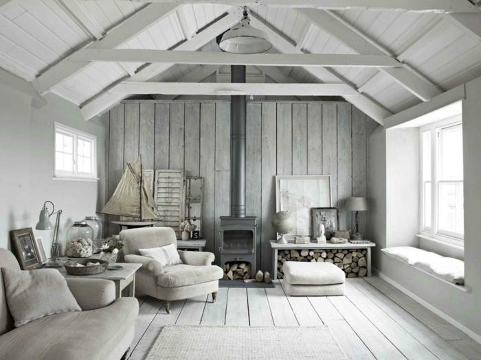 habitación gris, salón estilo rústico, paredes de listones, chimenea de metal, leña, muebles blanco roto, techo triangular con vigas, luz natural, colores neutrales