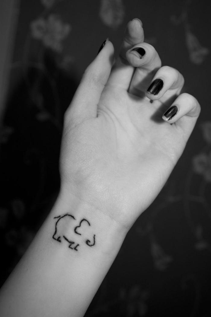 idea de tatuaje con elefante estilizado en la parte interior de la muñeca, mano de mujer con esmalte de uñas, foto en blanco y negro, tatuajes flechas