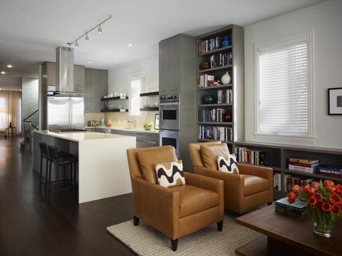 como amueblar un salon cocina, grande barra en blanco,a rmario alto con estantes con libros, sillones en color ocre tapizado de piel