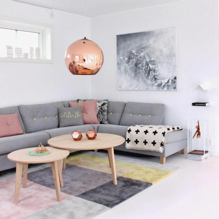 salon nordico, gris combinado con blanco y rosado, mesas redondas de madera clara, alfombra en cuadros de color, lampara cobriza, como decorar una habitacion