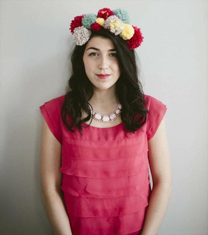 bonita corona hecha a mano con pompones de diferente color y tamaño, mujer con vestido en color cyclamen
