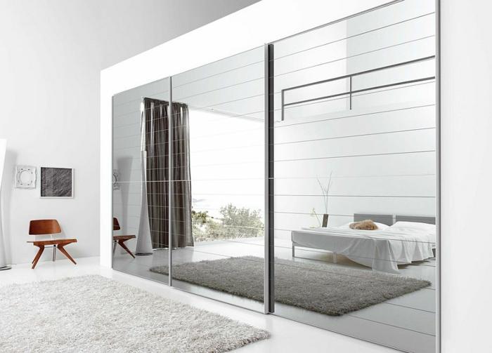dormitorio luminoso decorado en blanco en estilo minimalista, decoración de espejos plateados, alfombra peluda en blanco