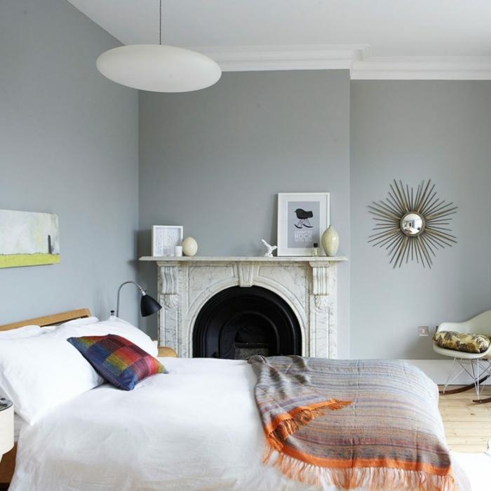 habitacion con mucha luz, dormitorio con chimenea, paredes grises, suelo con parquet, cama grande, silla de plástico, espejo sol