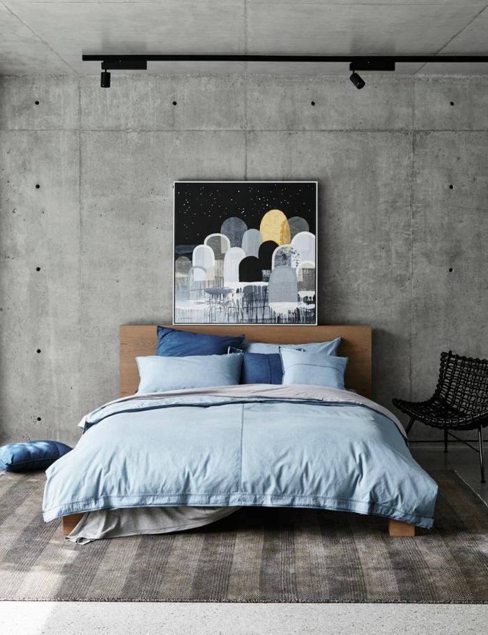 dormitorio insudtrial, pared de piedra gris, tapete rayado con aspecto desgastado, decoracion habitacion, cama doble con ropa de cama azul, pintura al oleo grande
