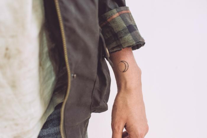 mini tatuajes, hombre con muñeca tatuada con media luna, estilo geométrico, chaqueta con mangas largas
