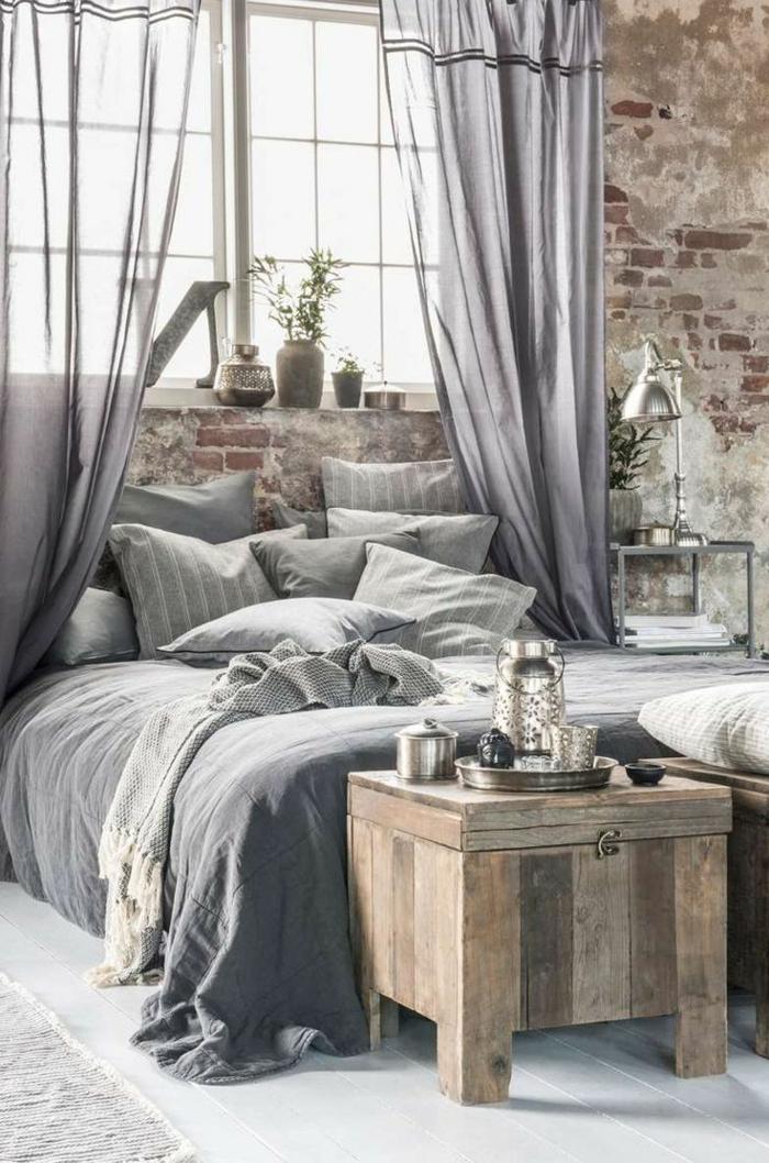 dormitorio con pared de ladrillo visto, habitacion gris y blanca, cama doble, ropa de cama gris, caja de madera convertida en mesa