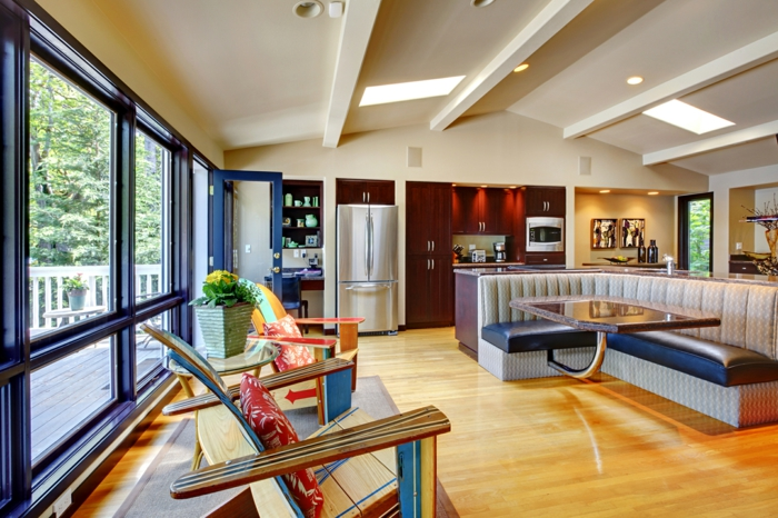 salon con techo inclinado, salon cocina en estilo moderno con tonos claros y cálidos, sofá tapizada de piel