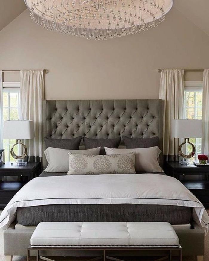 dormitorio lujoso, decoracion habitacion matrimonio, cabecero tapizado en capitoné, lámpara de araña, ventanas paralelas, pie de cama