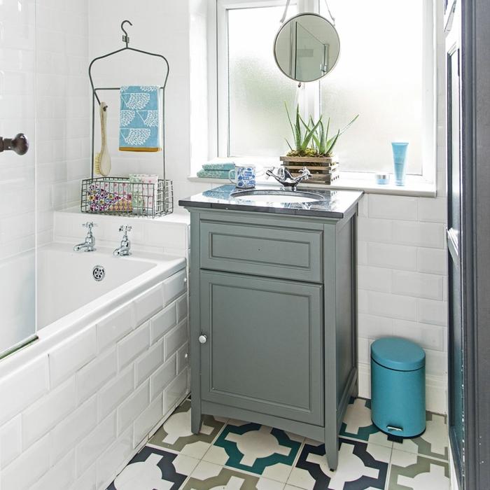 ducha con bañera, ventana mate, espejo colgante redondo pequeño, suelos con baldosas geométricas, armario bajo de madera pintada gris, cubo de basura azul